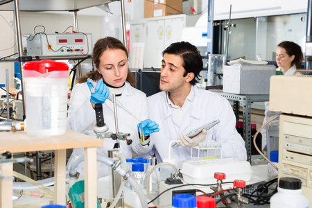 Two diligent  positive  young scientists working together in laboratory writing report on results of chemical experiments in notebook Фото со стока