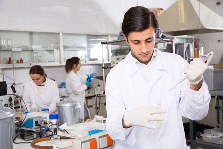 Intelligent student performing experiments in university laboratory, using mechanical lab pipette for mixing chemicals Фото со стока