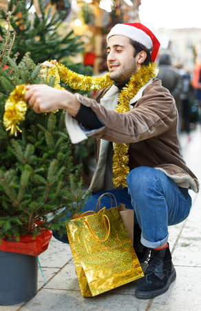 Portrait of joyful  man choosing toys and Christmas tree at fair outdoor