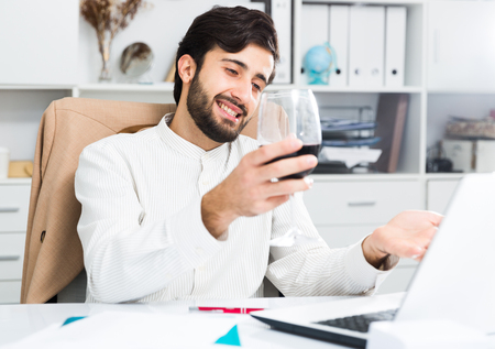 Cheerful brunette man holding glass of red wine and having video chat at office