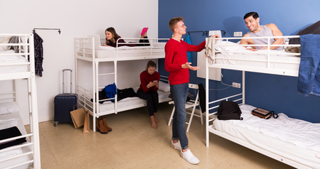 Young travelers communicating while resting in hostel dormitory
