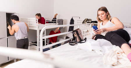 Young woman traveler resting with phone on two-story bed in hostel dorm Foto de archivo