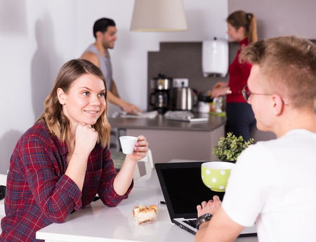 Positive girl friendly discussing with guy who sitting with laptop in common kitchen of hostel Foto de archivo