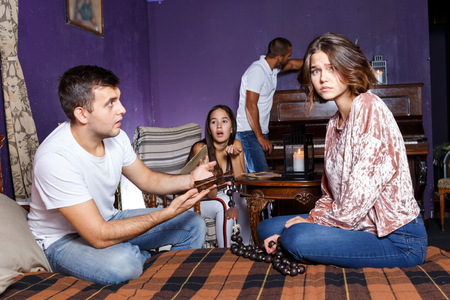 Young people looking at old wooden rosary while pursuing investigation in escape room with antique furniture Stock Photo