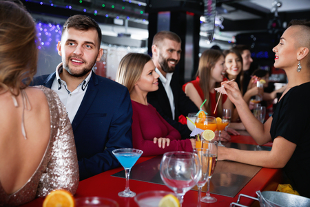 Young  positive cheerful people with cocktails having fun at nightclub