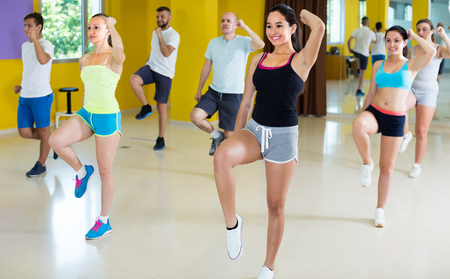 Positive women and men are dancing aerobics in dance class.
