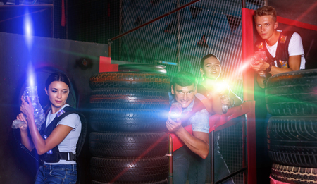 Smiling diligent positive cheerful young friends playing laser tag  game with colored laser guns near tires in labyrinth
