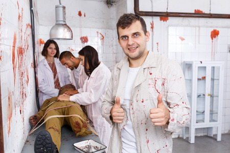 Portrait of cheerful guy with friends in quest room with bloody traces on walls and zombie mannequin on surgical table