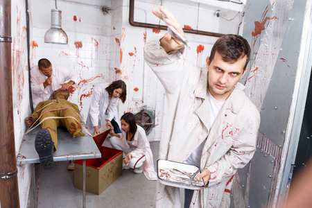Guy having fun with friends in quest room stylized as surgical room with traces of blood, frightening with medical instruments on camera Archivio Fotografico