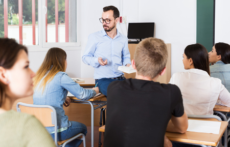 Young male teacher is giving interesting lecture for students in the classroom Stock Photo