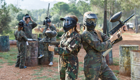 Two young women friends in camouflage holding guns before playing paintball with friends outdoor