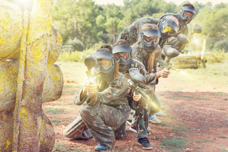 Expressive paintball team running with marker guns at the open playing field 스톡 콘텐츠