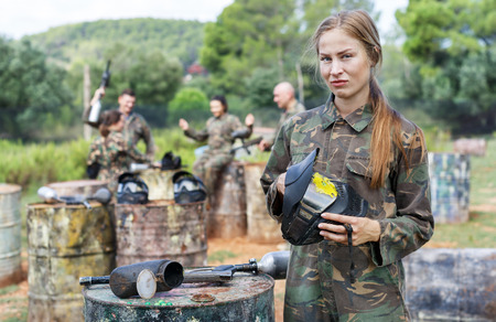 Portrait of upset girl standing with the protective helmet with a splash of paint after direct hit in paintball game Фото со стока - 115230236
