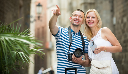 Smiling man and woman tourists taking camera in hands and photographing in city