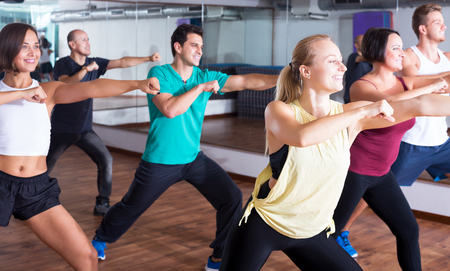 Portrait of smiling men and ladies dancing zumba at lesson