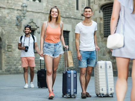 Adult couple in shorts with luggage walking through city street Stock Photo
