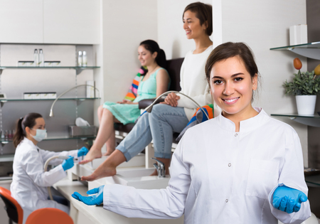 Portrait of happy professional nail master at working place inviting to salon
