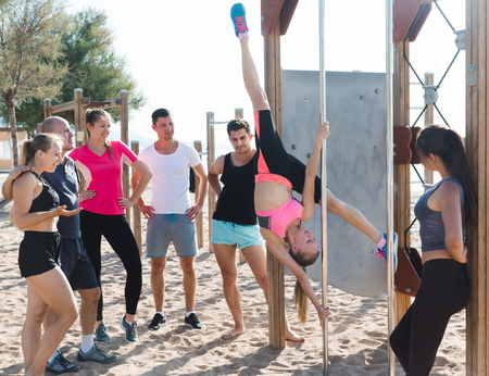 Sporty girl performing pole exercises causing admiration of people watching her Stock Photo