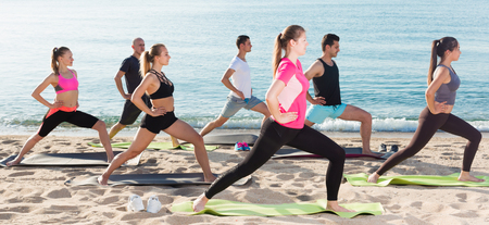 Group of sporty people practicing various yoga positions during training on beach 写真素材