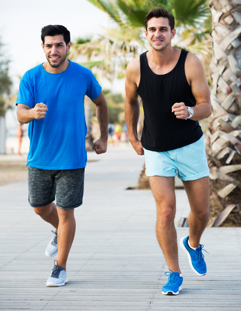 Portrait of two smiling sportsmen are jogging in time training in the park near ocean 写真素材