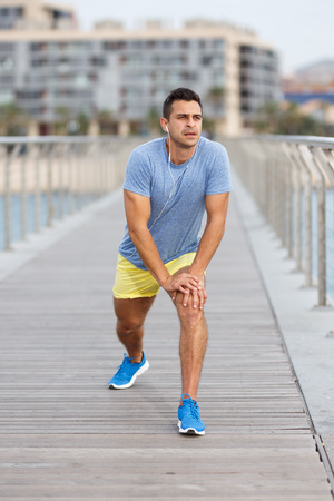 Positive sporty man listening music with earphones during workout outdoors