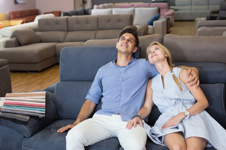 Portrait of a couple who are choosing comfortable sofa-transformer in the store.
