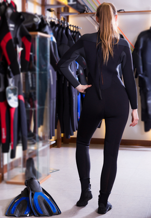 young woman is posing in new costume for diving in the store.