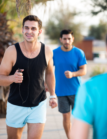 Smiling sportsmen are joggning race in time warm-up in the park near beach. 写真素材