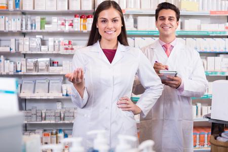 Smiling pharmacists in uniform posing in drugstore
