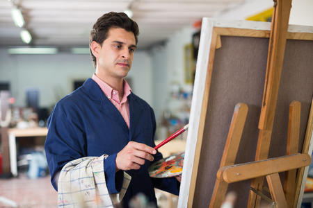 Happy art painter holding artist palette and painting on canvas Imagens - 115264493