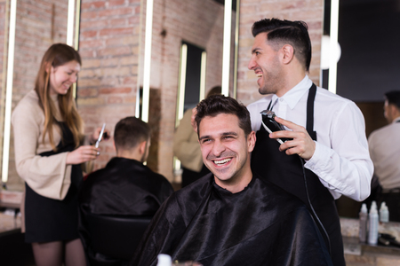 Professional hairdresser man doing styling of handsome guy with electric hair clipper at barber shop Stock fotó
