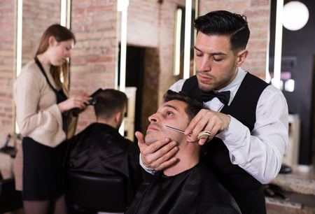 Male client getting old-fashioned shave with straight razor from male barber in modern salon