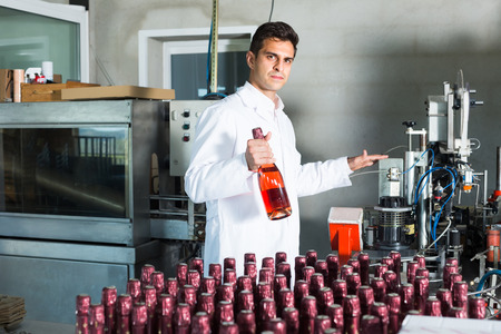 portrait of man in white robe working on wine production on manufactory