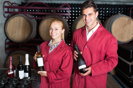 Two happy winery employees in uniform holding bottles of wine in aging section in cellar