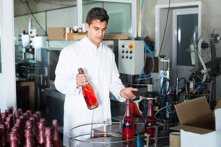Glad man holding newly produced bottle of wine on winery manufactory