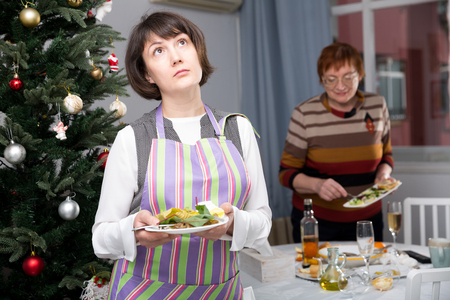 Mature mother with adult daughter laying christmas table