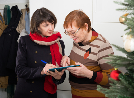 Smiling mature woman participating in survey conducted at home by polite social female worker Banque d'images