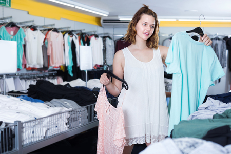 Cheerful young female customer selecting new garments at the store