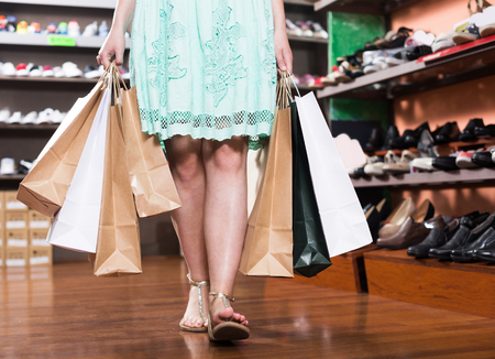 Happy woman is going out of the fashion store with full hands of purchases Stock Photo