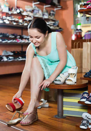 Happy  positive young girl is trying on red heeled sandals for summer season in shoes shop Stock Photo