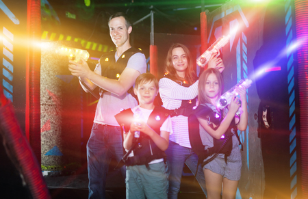 Excited kids and theirs parents in bright beams of laser guns during laser tag game in dark room Foto de archivo
