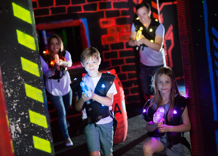 Happy little brother and sister with laser pistols playing laser tag in dark labyrinth with their parents Фото со стока