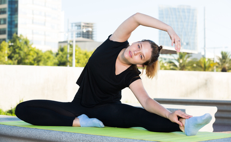 Young sporty female during outdoor training yoga positions