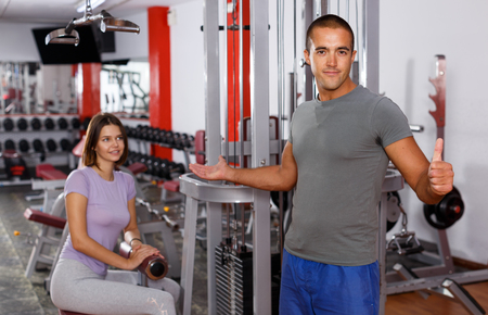 Portrait of cheerful sporty guy instructor of gym showing thumb up and attractive girl