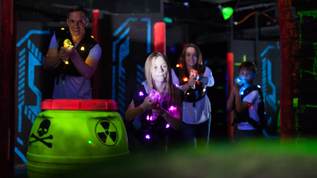 Modern young parents and children with laser pistols playing laser tag in dark labyrinth