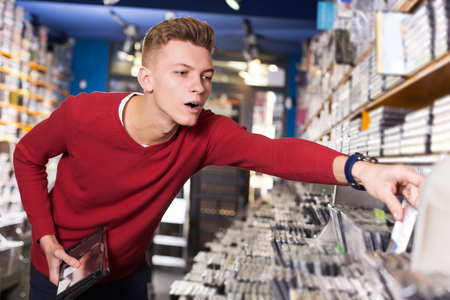 focused young guy looking for interesting movies on shelves of CD shop
