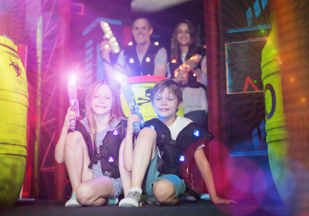 Cheerful little boy and girl having fun with adults on dark lasertag arena, posing while sitting with laser guns in colorful beams