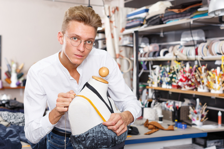 Male fashion designer at work - taking measurements of dummy for tailoring dress Reklamní fotografie