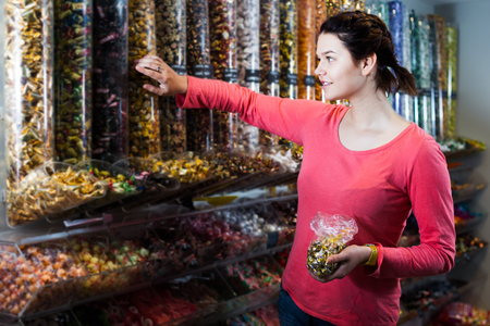 Portrait of young positive girl choosing candies for gift in sweets shop