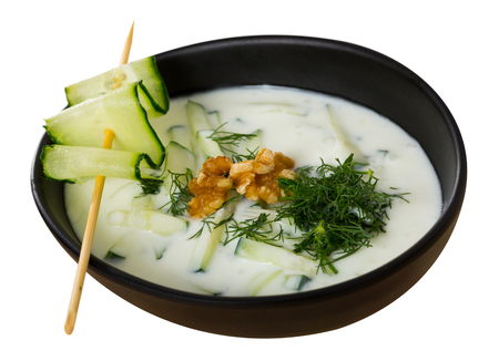 Southeast European cuisine. Traditional chilled soup Tarator with yogurt, fresh cucumber, dill and walnuts. Isolated over white background